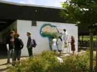 Wenige Schritte davon entfernt arbeitet die Wandmalgruppe. Lange war der Schuppen mit Grafitti beschmiert; gestern ist die Wand geweißt worden, und nun entsteht hier eine Karte des